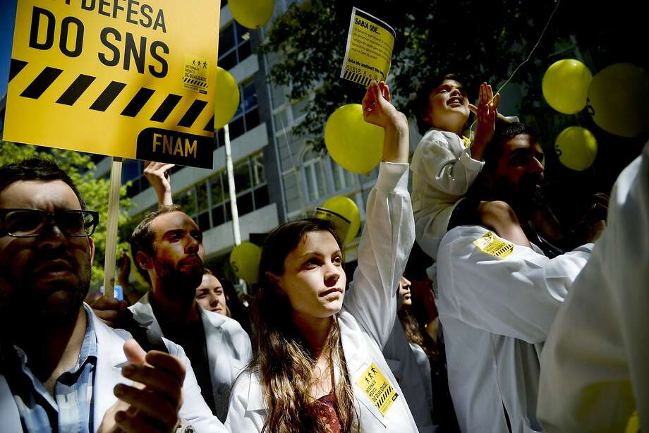 Hundreds of doctors in white smocks protest on July 8, 2014, in front of the Portuguese Ministry of Health on the first day of a two-day nationwide strike to demand better conditions on the national health care.  AFP PHOTO/ PATRICIA DE MELO MOREIRAPATRICIA DE MELO MOREIRA/AFP/Getty Images Photo: Patricia De Melo Moreira, AFP/Getty Images