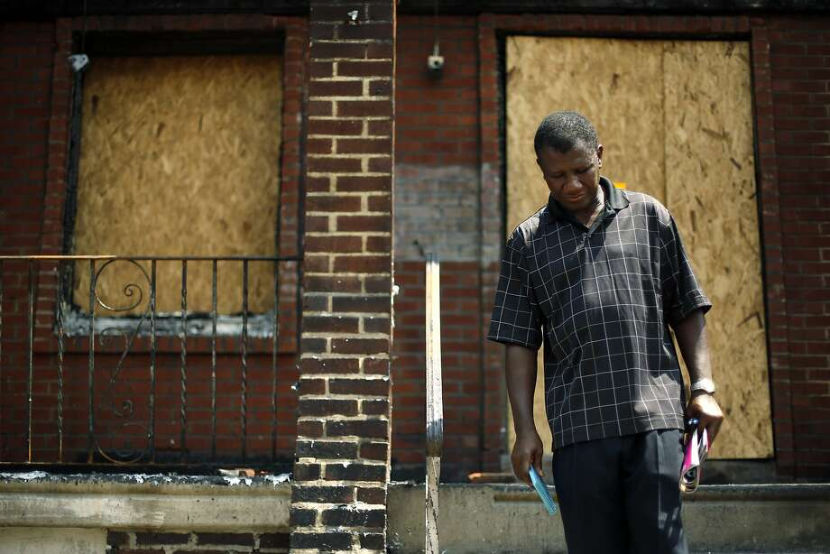 Solomon Johnson pauses on the steps of his fire-damaged rowhouse, Tuesday, July 8, 2014, in Philadelphia, as a neighbor recounts details from the weekend fire where four young children died in a fast-moving blaze that engulfed at least 10 residences. Johnson lived next door to the children. (AP Photo/Matt Slocum) Photo: Matt Slocum, Associated Press