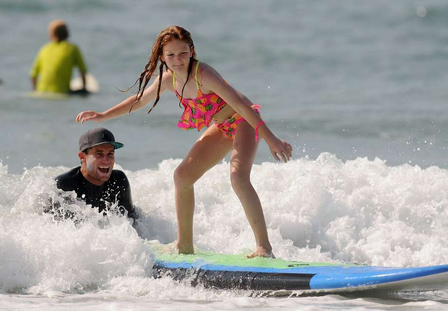Clare Lewis, 10, rides the waves on her surfboard with the help of surfer Brad Ettinger at the Hurley Surf and Enjoy Summer Tour event in conjunction with Sweetwater Surf shop in Wrightsville Beach, N.C., Tuesday, July 8, 2014. Surfers 18 and under surfed with professional surfers at the event.  (AP Photo/The Star-News, Mike Spencer) LOCAL TELEVISION OUT; LOCAL INTERNET OUT Photo: Mike Spencer, Associated Press