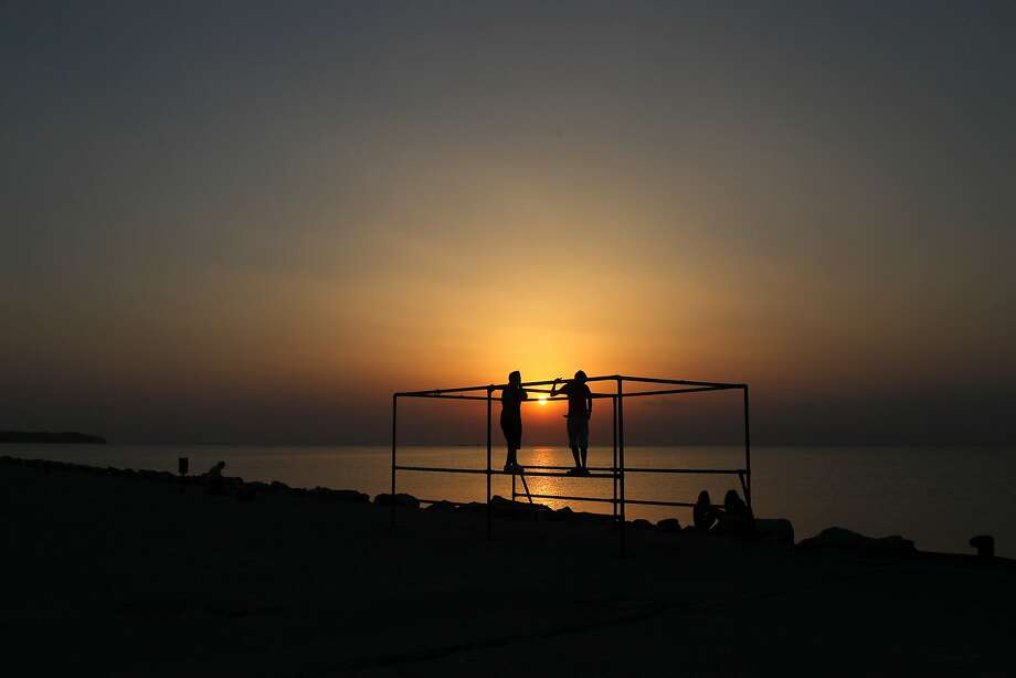 Boys climb on a metal construction at a public beach of Perea, during sunset, in the eastern suburbs of Thessaloniki, Greece, Tuesday, July 8, 2014. (AP Photo/Nikolas Giakoumidis) Photo: Nikolas Giakoumidis, Associated Press