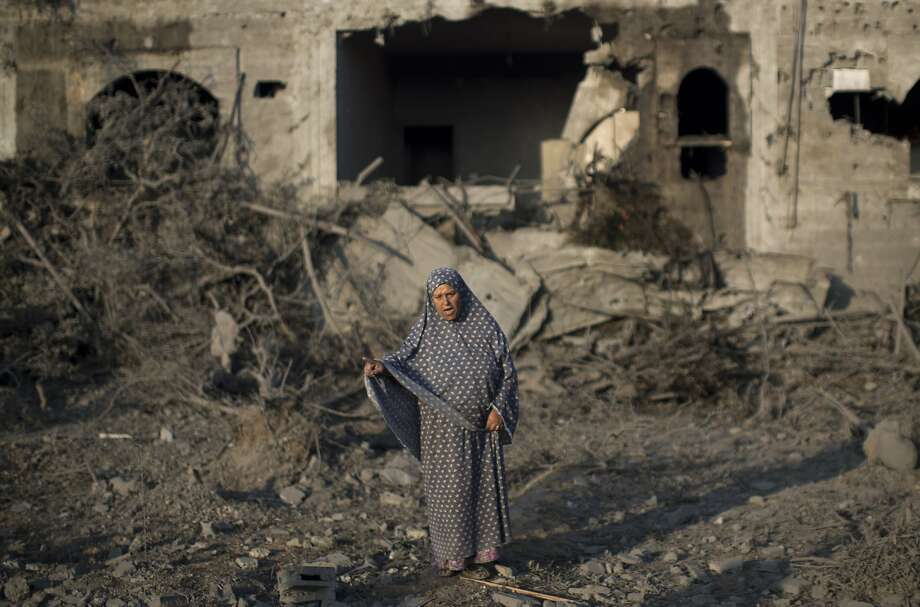 TOPSHOTS A Palestinian woman gestures as she stands amidst destruction following an Israeli military strike in  Gaza City on July 08, 2014 . The Israeli air force launched dozens of raids on the Gaza Strip overnight after massive rocket fire from the enclave pounded southern Israel, leaving 17 people injured, sources said. AFP PHOTO / MAHMUD HAMSMAHMUD HAMS/AFP/Getty Images Photo: Mahmud Hams, AFP/Getty Images