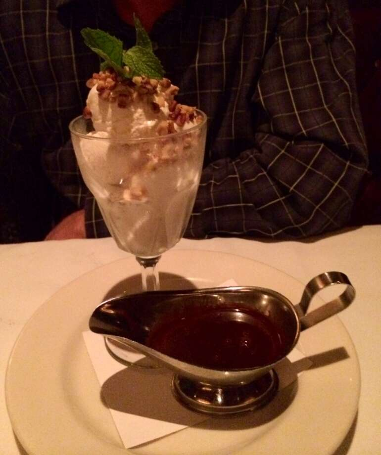 An ice cream sundae with Belgian dark chocolate, whipped cream and pecans