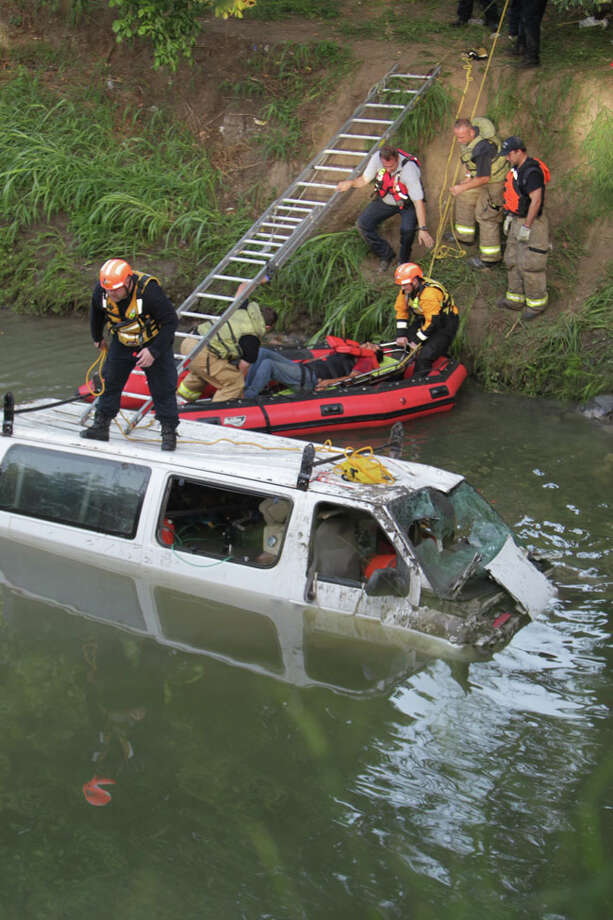 Houston emergency crews worked to rescue seven men trapped in a white van that plunged off the bridge and landed in a bayou near Cavalcade and North Freeway early Wednesday morning. Photo: James Nielsen / Houston Chronicle / Houston Chronicle 2011