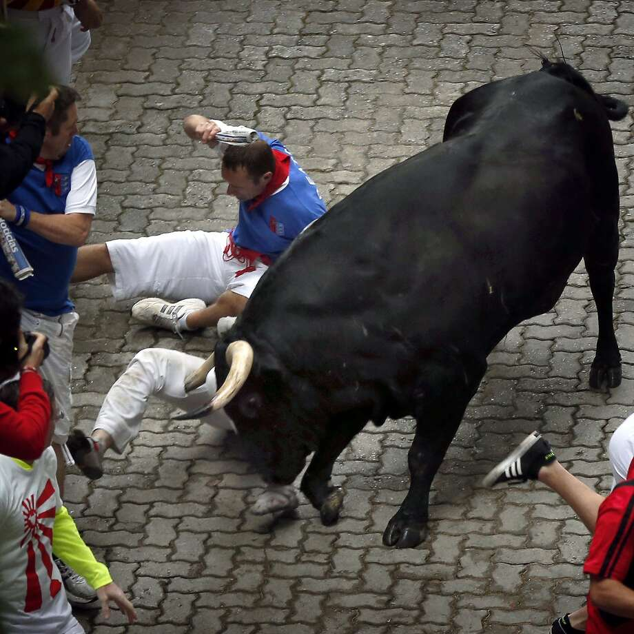 "U.S. runner Bill Hillmann, 35, from Chicago is gored on his right leg by a Victoriano del Rio ranch fighting bull during the running of the bulls of the San Fermin festival, in Pamplona, Spain, Wednesday, July 9, 2014. Revelers from around the world arrive in Pamplona every year to take part on some of the eight days of the running of the bulls glorified by Ernest Hemingway's 1926 novel ""The Sun Also Rises."" (AP Photo/Daniel Ochoa de Olza) Photo: Daniel Ochoa De Olza, Associated Press"