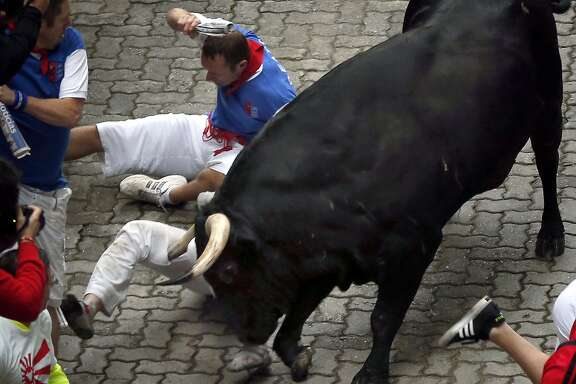 "U.S. runner Bill Hillmann, 35, from Chicago is gored on his right leg by a Victoriano del Rio ranch fighting bull during the running of the bulls of the San Fermin festival, in Pamplona, Spain, Wednesday, July 9, 2014. Revelers from around the world arrive in Pamplona every year to take part on some of the eight days of the running of the bulls glorified by Ernest Hemingway's 1926 novel ""The Sun Also Rises."" (AP Photo/Daniel Ochoa de Olza)"