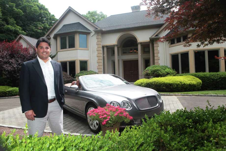 Higgins Group agent Todd Miller stands near a 2008 Bentley, which the homeowner is giving to  the agent that sells his home at 456 Hillside Road in Fairfield, Conn. on Monday, June 30, 2015. Photo: BK Angeletti, B.K. Angeletti / Connecticut Post freelance B.K. Angeletti