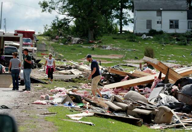 People sort through debris of a destroyed house after Tuesday night's storm, on Wednesday, July 9, 2014, in Smithfield, N.Y. The National Weather Service has confirmed that a tornado destroyed the homes in upstate New York where four people were killed. Barbara Watson, the meteorologist leading the agency's survey team says that the violent winds Tuesday were at least 100 mph and reached undetermined higher speeds to cause the damage they're seeing in the town of Smithfield. (AP Photo/Mike Groll) ORG XMIT: NYMG102 Photo: Mike Groll, AP / AP