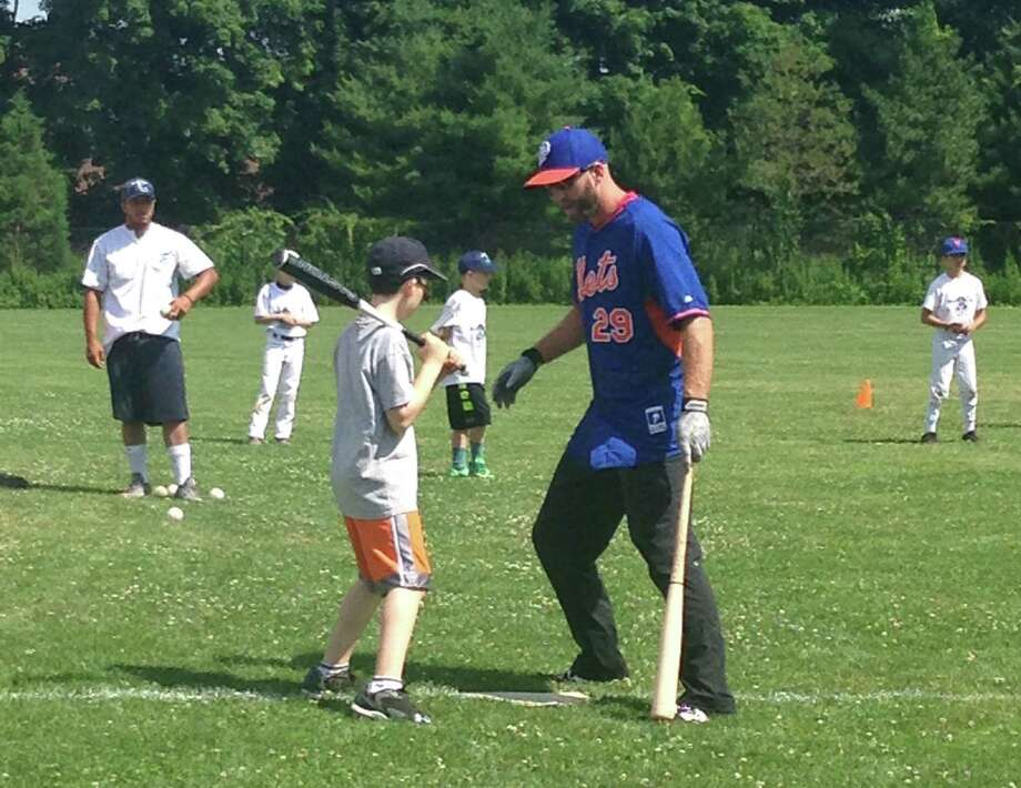 New York Mets player Eric Campbell, right, offers instruction to a batter during a clinic held by Baseball World Training School on Wednesday morning at Bedford Middle School in Westport. Photo: Ryan Lacey/Staff Photo / Westport News Contributed