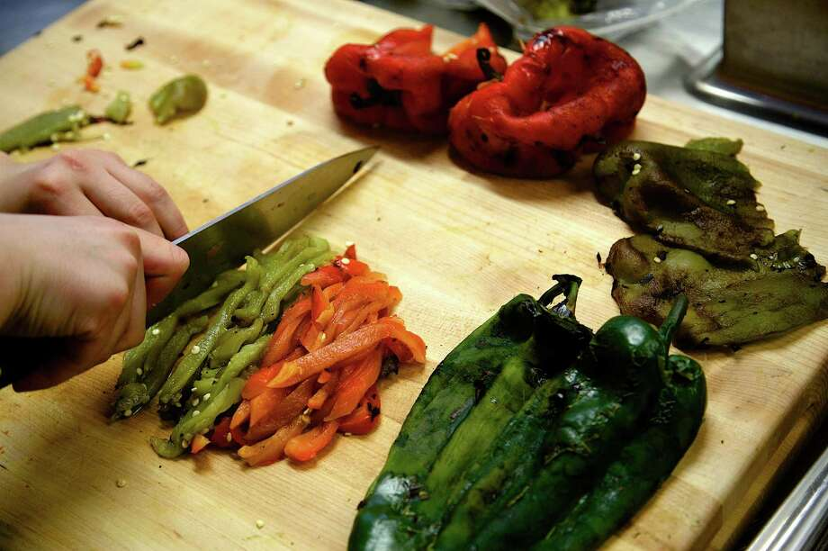 Marilyn J. Kitts slices roasted chili peppers in the Latin American kitchen at the Culinary Institute of America San Antonio campus, Friday, May 16, 2014. Photo: J. MICHAEL SHORT, FOR THE EXPRESS-NEWS / Photo Copyright ©2014 J. MICHAEL SHORT