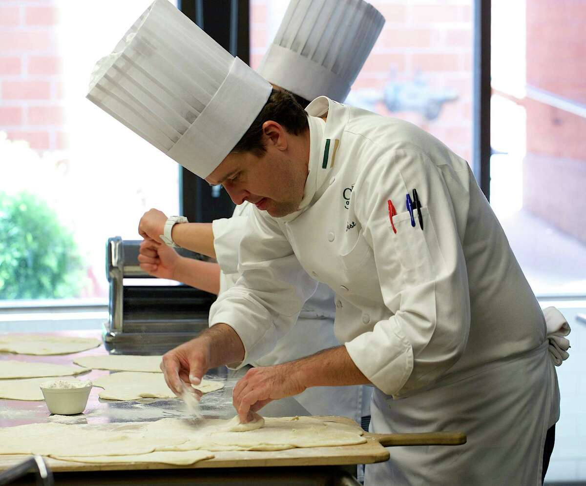 Instructor Brian West works with pizza dough in the