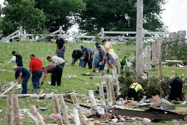 People sort through debris after Tuesday night's storm, on Wednesday, July 9, 2014, in Smithfield, N.Y. The National Weather Service has confirmed that a tornado destroyed the homes in upstate New York where four people were killed. Barbara Watson, the meteorologist leading the agency's survey team says that the violent winds Tuesday were at least 100 mph and reached undetermined higher speeds to cause the damage they're seeing in Smithfield. (AP Photo/Mike Groll) ORG XMIT: NYMG104 Photo: Mike Groll, AP / AP