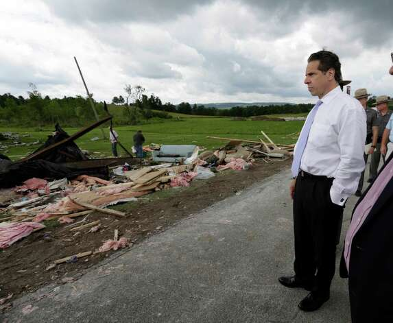 New York Gov. Andrew Cuomo surveys the damage from Tuesday night's storm, on Wednesday, July 9, 2014, in Smithfield, N.Y. The National Weather Service has confirmed that a tornado destroyed the homes in upstate New York where four people were killed. (AP Photo/Mike Groll) ORG XMIT: NYMG107 Photo: Mike Groll, AP / AP