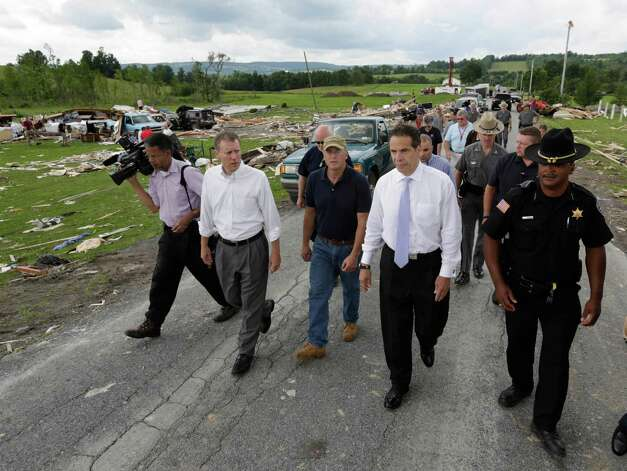 New York Gov. Andrew Cuomo, second from right, walks with state Sen. David Valesky, left, Smithfield Town Supervisor Rick Bargabos and Madison County Sheriff Allen Riley as they survey the damage from Tuesday night's storm, on Wednesday, July 9, 2014, in Smithfield, N.Y. The National Weather Service has confirmed that a tornado destroyed the homes in upstate New York where four people were killed. Barbara Watson, the meteorologist leading the agency's survey team says that the violent winds Tuesday were at least 100 mph and reached undetermined higher speeds to cause the damage they're seeing in Smithfield. (AP Photo/Mike Groll) ORG XMIT: NYMG108 Photo: Mike Groll, AP / AP