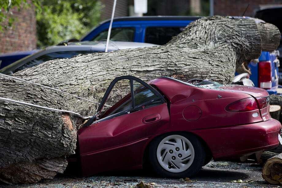You never know when you'll get a flat: The good news is, the driver wasn't inside. (Wind storm damage in Philadelphia.) Photo: Matt Rourke, Associated Press