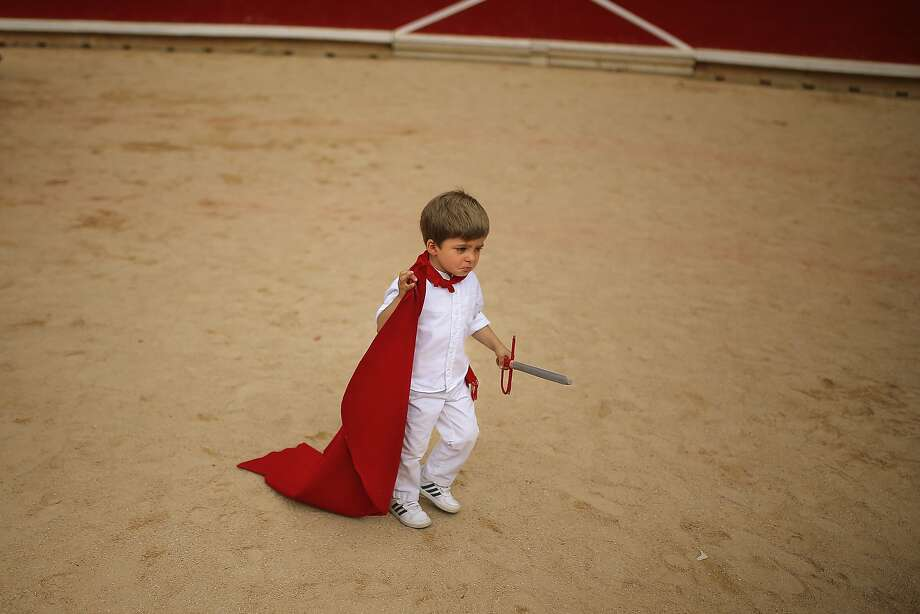 Bring it on, bulls: A young matador leaves the bull-fighting arena after a bullfighting class for children given by Spanish bullfighter Alejandro Talavante in Pamplona, Spain. Photo: Andres Kudacki, Associated Press