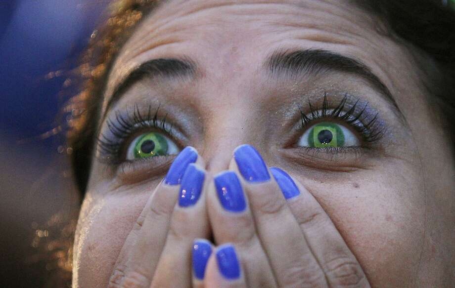 Oh, the horror! A Brazil fan watches her team implode in a World Cup semifinal on Copacabana beach in Rio. Photo: Leo Correa, Associated Press