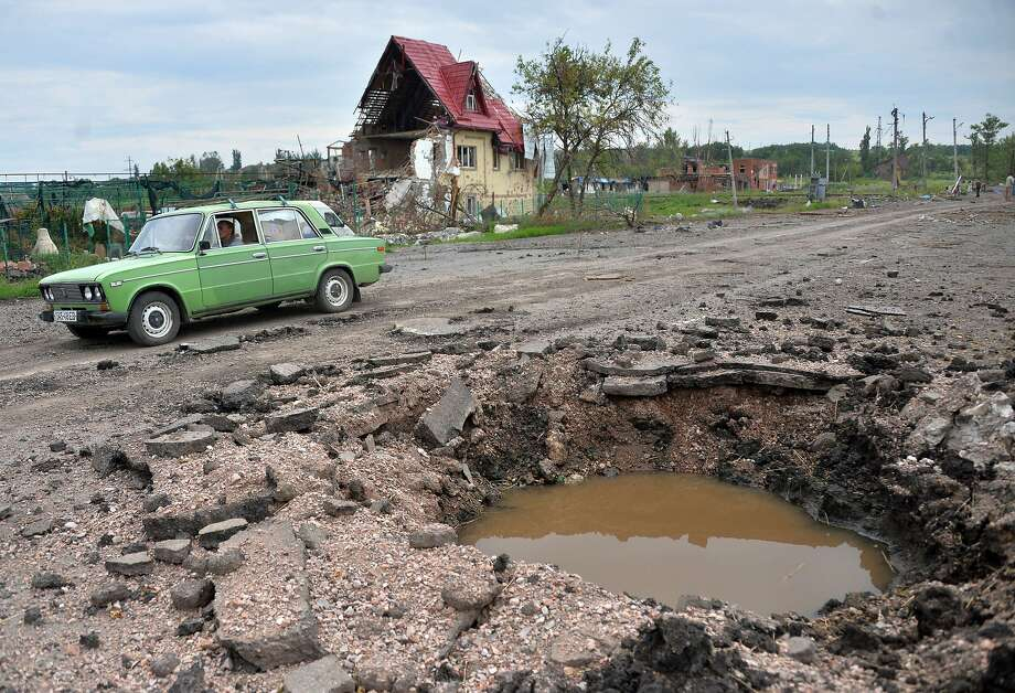 Monster pothole: A car drives past a shell crater in the village of Semyonovka, the scene of fierce fighting between Ukrainian troops and pro-Russian militants near the eastern Ukrainian city of Slavyansk. Photo: Genya Savilov, AFP/Getty Images