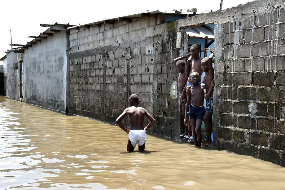 After the deluge in Abidjan: Boys stand in a flooded street in the impoverished Adjouffou neighborhood of Abidjan, Ivory Coast. Several weeks of torrential rainfall in the Ivorian economic capital have left several people dead and caused substantial damage to the city. Photo: Issouf Sanogo, AFP/Getty Images