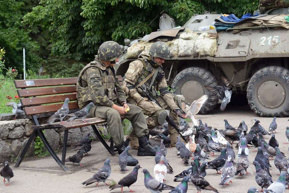 Ukrainian soldiers feed pigeons next to their APC, near the city hall on July 8, 2014 in the eastern Ukrainian city of Slavyansk. Ukraine on July 8 brushed off strong European pressure and rejected talks with pro-Russian rebels on a truce to halt a bloody insurgency convulsing the ex-Soviet nation until they lay down their arms. The unconditional stance reflected a new confidence in Kiev that it was on the verge of quashing an uprising it views as Moscow's retribution for the February ouster of a Kremlin-backed leader and the decision to pursue a historic alliance with the West. Photo: Sergey Bobok, AFP/Getty Images