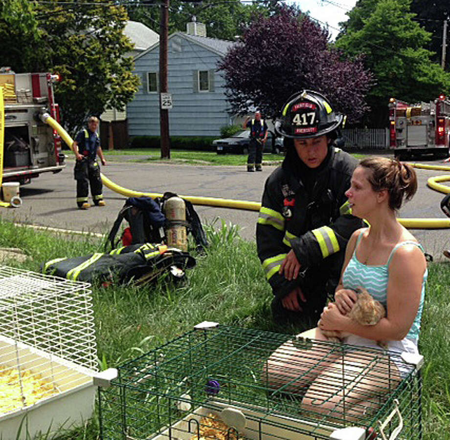 A resident of a Knapps Highway home hit by fire Wednesday comforts one of the pets rescued by firefighters from the smoky basement blaze. Photo: Fairfield Fire Department / Fairfield Citizen