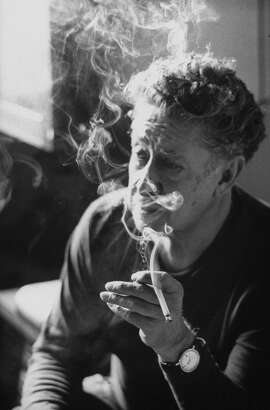 Mexican muralist David Alfaro Siqueiros taking a break from work and smoking a cigarette in 1965.
