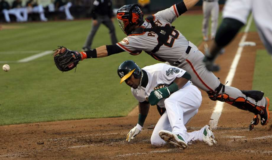 Yoenis Cespedes (52) ducks under Giants catcher Buster Posey as he scores on a throw in the third inning as the Oakland Athletics played the San Francisco Giants on Tuesday, July 8, 2014, at O.co Coliseum in Oakland, Calif. Photo: The Chronicle