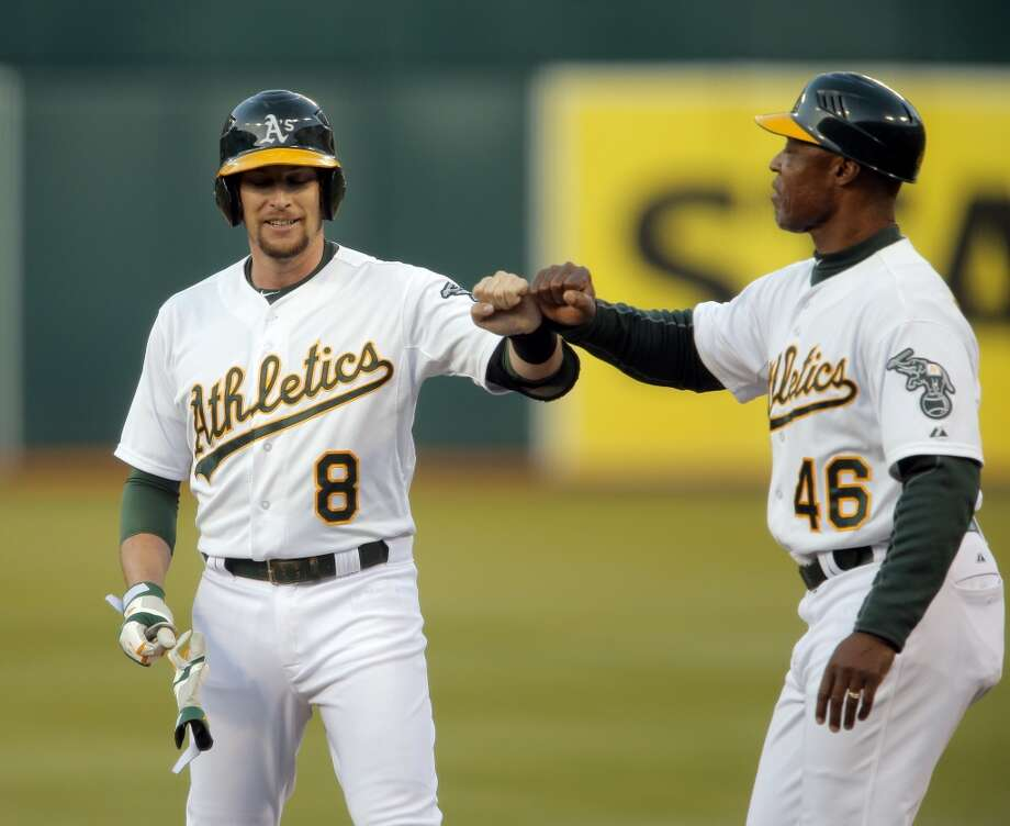 Jed Lowrie (8) gets a high five from first base coach Ty Waller after he got a hit in the third inning as the Oakland Athletics played the San Francisco Giants on Tuesday, July 8, 2014, at O.co Coliseum in Oakland, Calif. Photo: The Chronicle