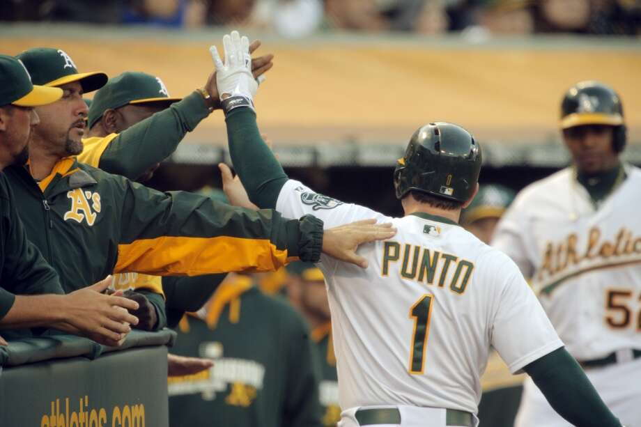 Nick Punto (1) is high fived after scoring in the third inning as the Oakland Athletics played the San Francisco Giants on Tuesday, July 8, 2014, at O.co Coliseum in Oakland, Calif. Photo: The Chronicle