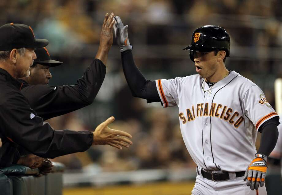 Tyler Colvin (10) high fives coaches after hitting a solo homerun in the seventh inning for the Giants only run as the Oakland Athletics played the San Francisco Giants on Tuesday, July 8, 2014, at O.co Coliseum in Oakland, Calif. Photo: The Chronicle
