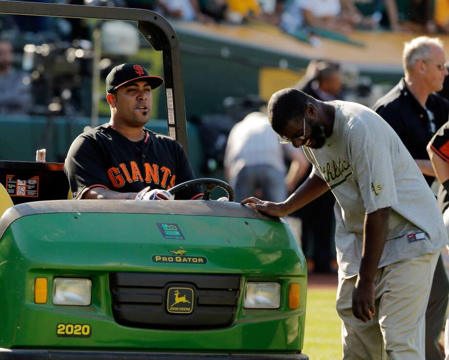 Hector Sanchez laughs with one of the Coliseum grounds crew members as Sanchez sits in his cart  before the Oakland Athletics played the San Francisco Giants on Tuesday, July 8, 2014, at O.co Coliseum in Oakland, Calif. Photo: The Chronicle