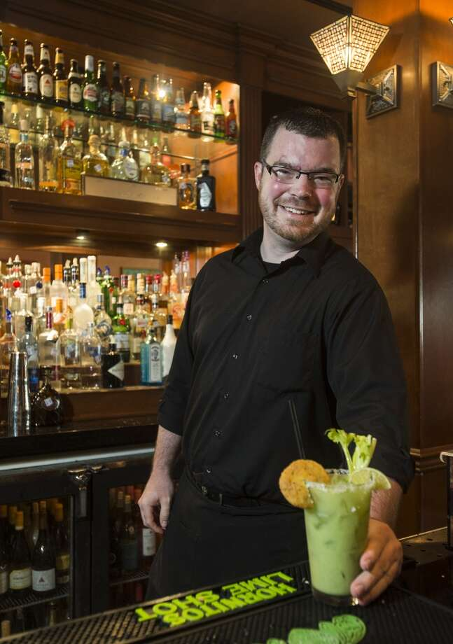 Ben Simpson, a bartender at Suga's, poses with a Southern Green Bloody Mary at Suga's on Tuesday afternoon. Simpson is the focus of the Cat5 Service Station piece for July 3, 2014. Photo taken Tuesday 6/24/14 Jake Daniels/@JakeD_in_SETX