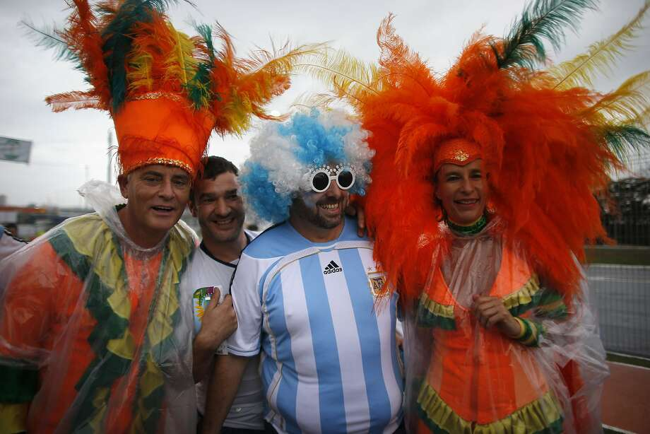 Argentina soccer fans, center, pose for photos between Dutch fans at the entrance to Itaquerao stadium prior to the the World Cup semifinal match between Argentina and Netherlands in Sao Paulo, Brazil, Wednesday, July 9, 2014. Photo: Dario Lopez-Mills, Associated Press