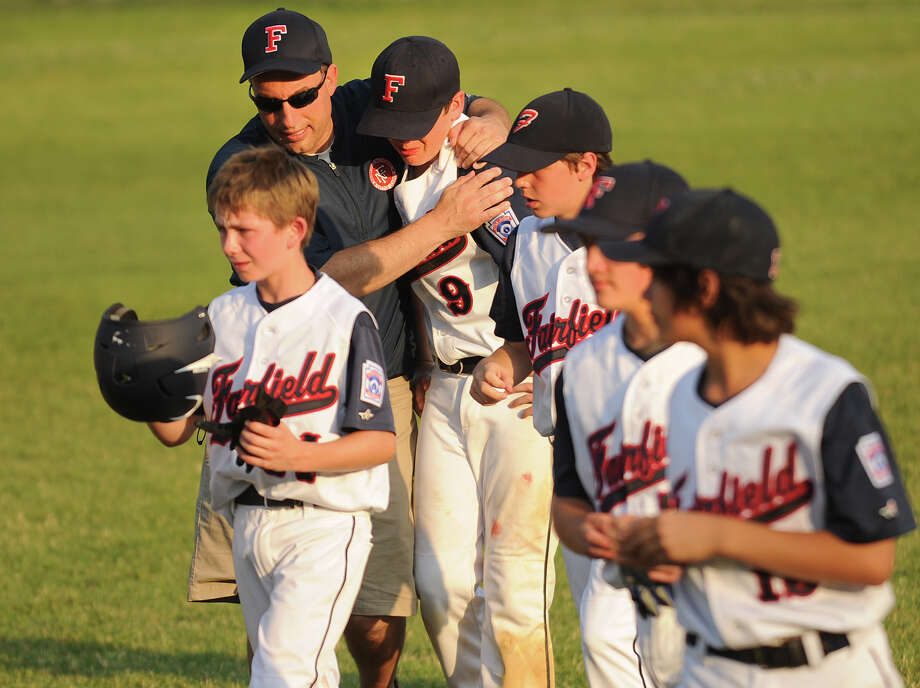 Fairfield National Coach Brad Weinstein hugs player Chris Saladin following his team's dramatic, 4-3 loss to Monroe in the opening game of the Little League District 2 double elimination tournament at Unity Park in Trumbull, Conn. on Monday, July 7, 2014. Photo: Brian A. Pounds / Connecticut Post