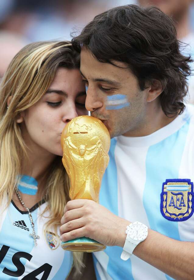 Argentina fans kiss a replica of the World Cup trophy prior to the 2014 FIFA World Cup Brazil Semi Final match between the Netherlands and Argentina at Arena de Sao Paulo on July 9, 2014 in Sao Paulo, Brazil.  Photo: Dean Mouhtaropoulos, Getty Images