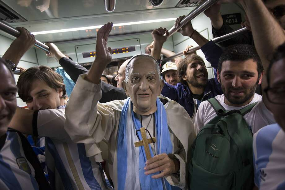 A man dressed as Pope Francis cheers with others Argentina national soccer fans as they ride the subway to the Itaquerao Stadium, to watch the World Cup semifinal match between the Netherlands and Argentina, in Sao Paulo Brazil, Wednesday, July 9, 2014.  Photo: Felipe Dana, Associated Press