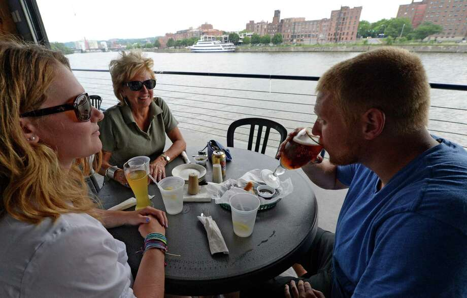 Kara Olszewski, left, and Debbie Skinner Grant, center, watch as John Skinner enjoys a Davidson Brothers IPA draft Monday afternoon July 7, 2014 at the Rusty Anchor Waterfront Bar in Watervliet, N.Y. (Skip Dickstein / Times Union) Photo: SKIP DICKSTEIN / 00027645A