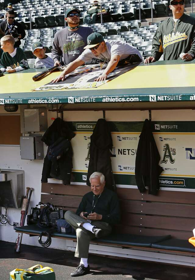 A's owner Lew Wolff checks his messages in the dugout as fans wait for autographs  before the start of the game, as the Oakland Athletics prepare to take on the Cleveland Indians at the O.co Coliseum, on Wednesday April 2, 2014, in Oakland, Calif. Photo: Michael Macor, The Chronicle