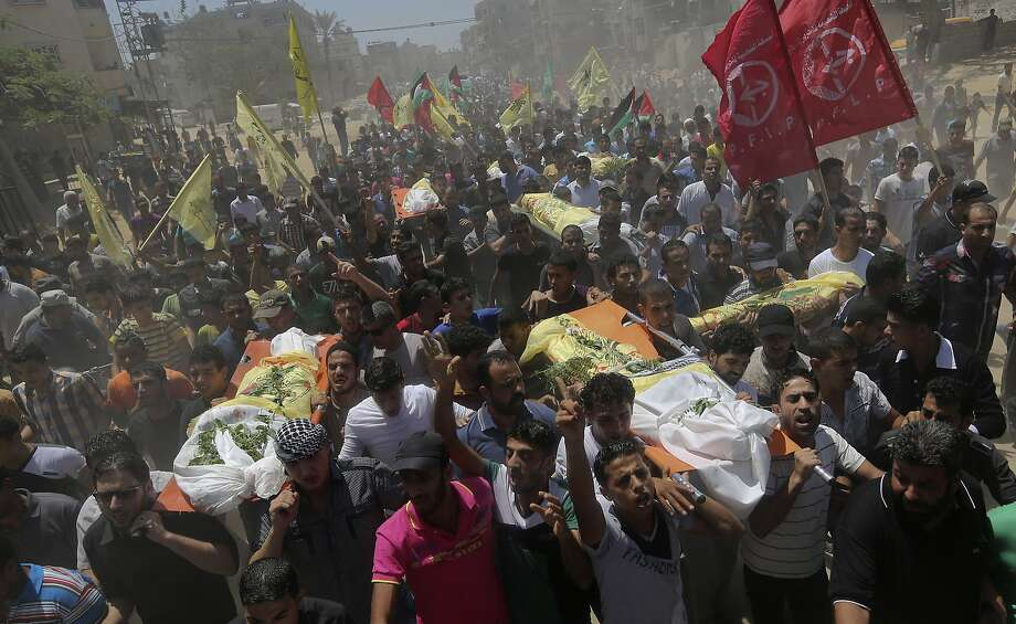 Palestinians carry bodies of seven people at a funeral in the Gaza Strip. They were killed in an air strike. Photo: Hatem Moussa, Associated Press
