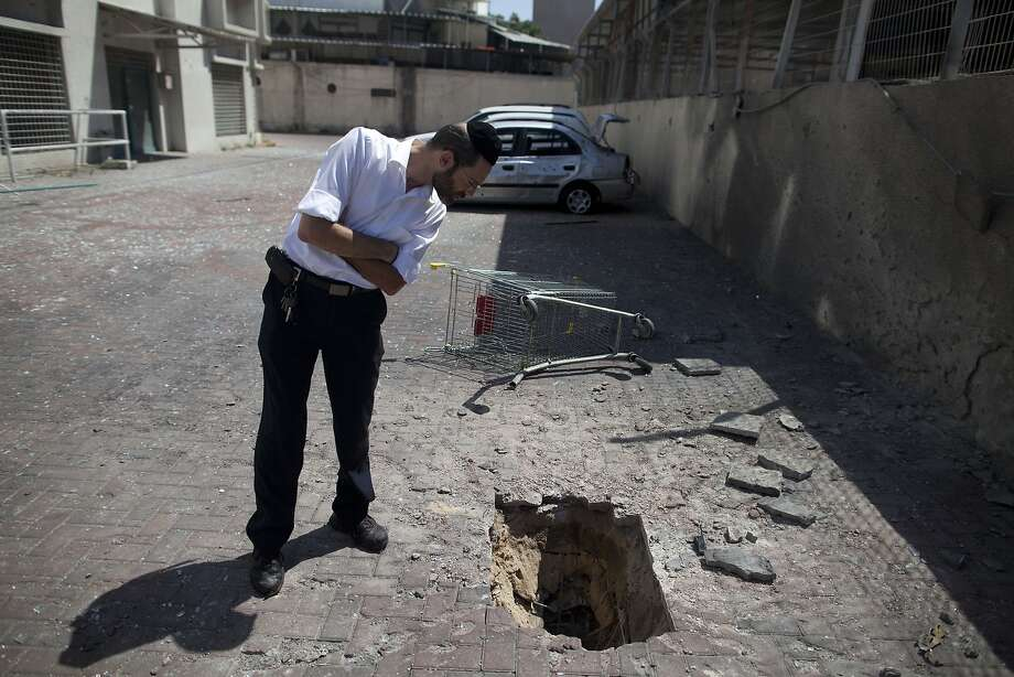 Hamas pothole: In Ashdod, Israel, an Ultra Orthodox Jewish man inspects the impact of a rocket fired from the Gaza 