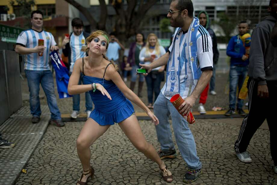A Brazilian national soccer fan, left center, dances with an Argentine fan as they wait for start of the live telecast of the World Cup semifinal match between Argentina and the Netherlands, at FIFA Fan Fest in Sao Paulo, Brazil, Wednesday, July 9, 2014. Photo: Rodrigo Abd, Associated Press