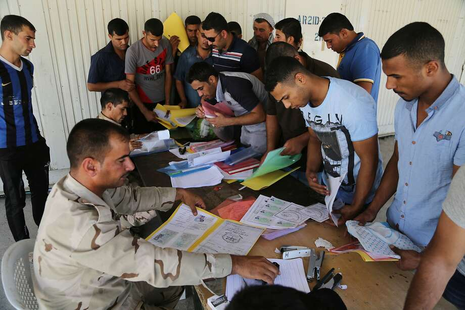 Iraqi men volunteer for military services at the main army recruiting center in Baghdad. Photo: Karim Kadim, Associated Press