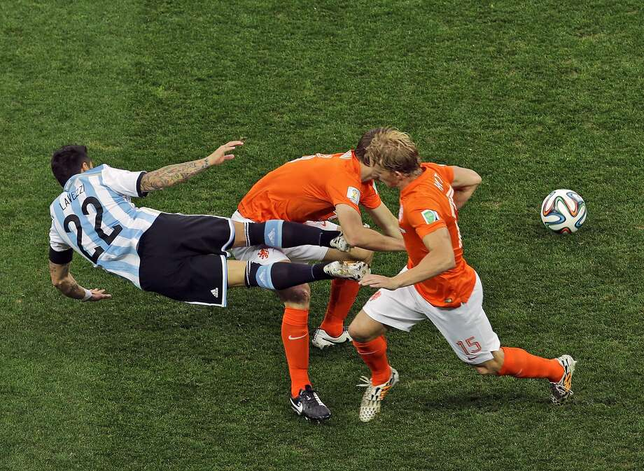 Argentina's Ezequiel Lavezzi, left, falls as he fights for the ball with Netherlands' Dirk Kuyt, right, during the World Cup semifinal soccer match between the Netherlands and Argentina at the Itaquerao Stadium in Sao Paulo Brazil, Wednesday, July 9, 2014.  Photo: Hassan Ammar, Associated Press
