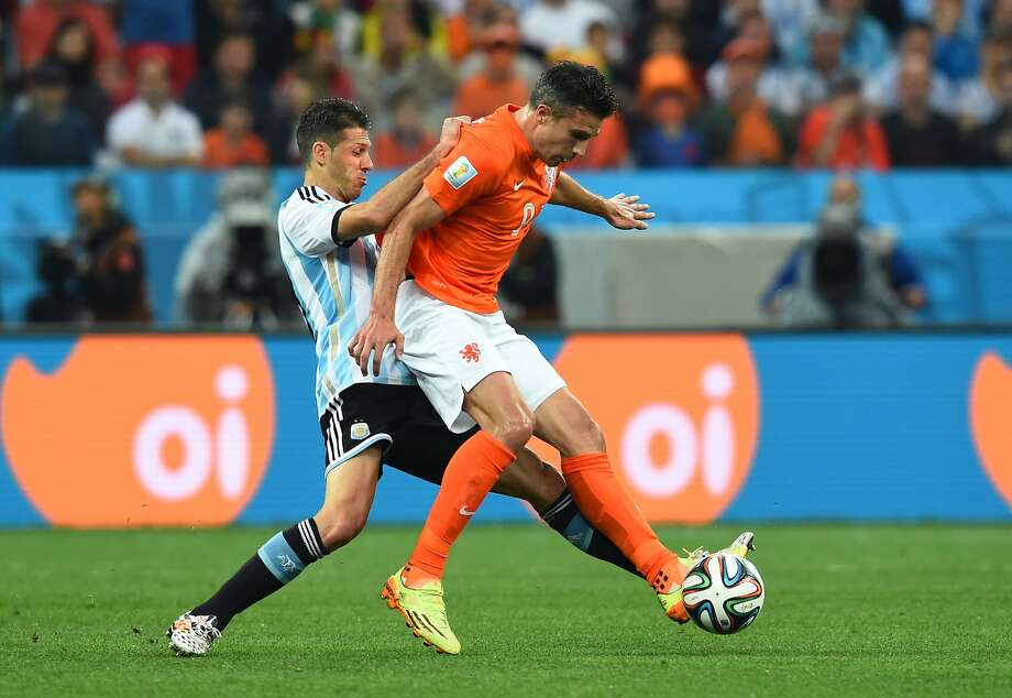 Martin Demichelis of Argentina challenges Robin van Persie of the Netherlands during the 2014 FIFA World Cup Brazil Semi Final match between the Netherlands and Argentina at Arena de Sao Paulo on July 9, 2014 in Sao Paulo, Brazil.  Photo: Matthias Hangst, Getty Images