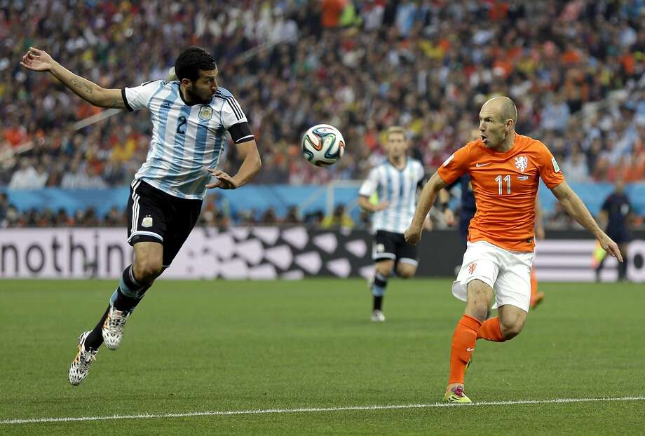 Argentina's Ezequiel Garay (2)  tries to stop a pass to Netherlands' Arjen Robben (11) during the World Cup semifinal soccer match between the Netherlands and Argentina at the Itaquerao Stadium in Sao Paulo Brazil, Wednesday, July 9, 2014. Photo: Natacha Pisarenko, Associated Press