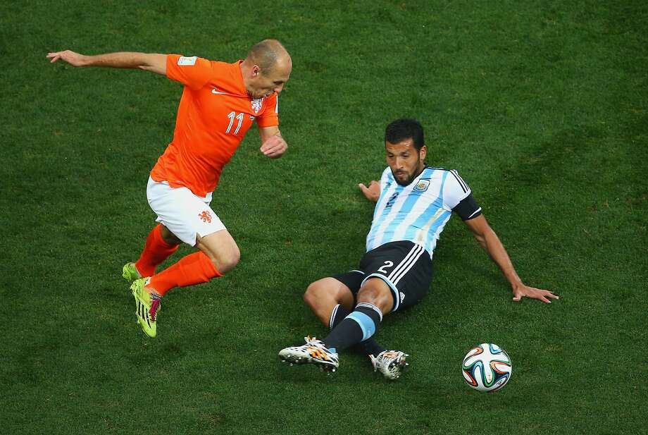 Ezequiel Garay of Argentina tackles Arjen Robben of the Netherlands during the 2014 FIFA World Cup Brazil Semi Final match between the Netherlands and Argentina at Arena de Sao Paulo on July 9, 2014 in Sao Paulo, Brazil.  Photo: Julian Finney, Getty Images