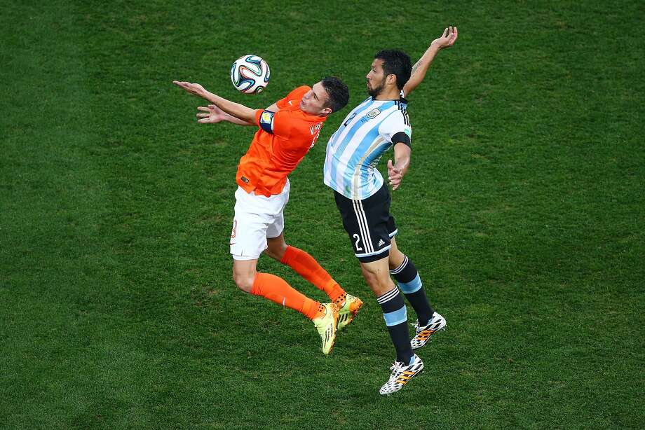 Robin van Persie of the Netherlands and Ezequiel Garay of Argentina compete for the ball during the 2014 FIFA World Cup Brazil Semi Final match between the Netherlands and Argentina at Arena de Sao Paulo on July 9, 2014 in Sao Paulo, Brazil. Photo: Julian Finney, Getty Images