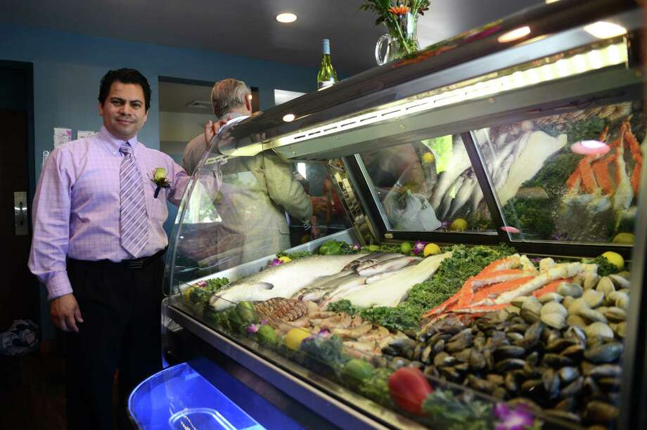 Elmer Palma, owner of Waterfall Restaurant, poses by the fresh seafood display at his restaurant in Danbury, Conn. Tuesday, July 8, 2014.  The restaurant, which takes advantage of the view of Padanaram Brook, celebrated its grand opening Tuesday. Photo: Tyler Sizemore / The News-Times