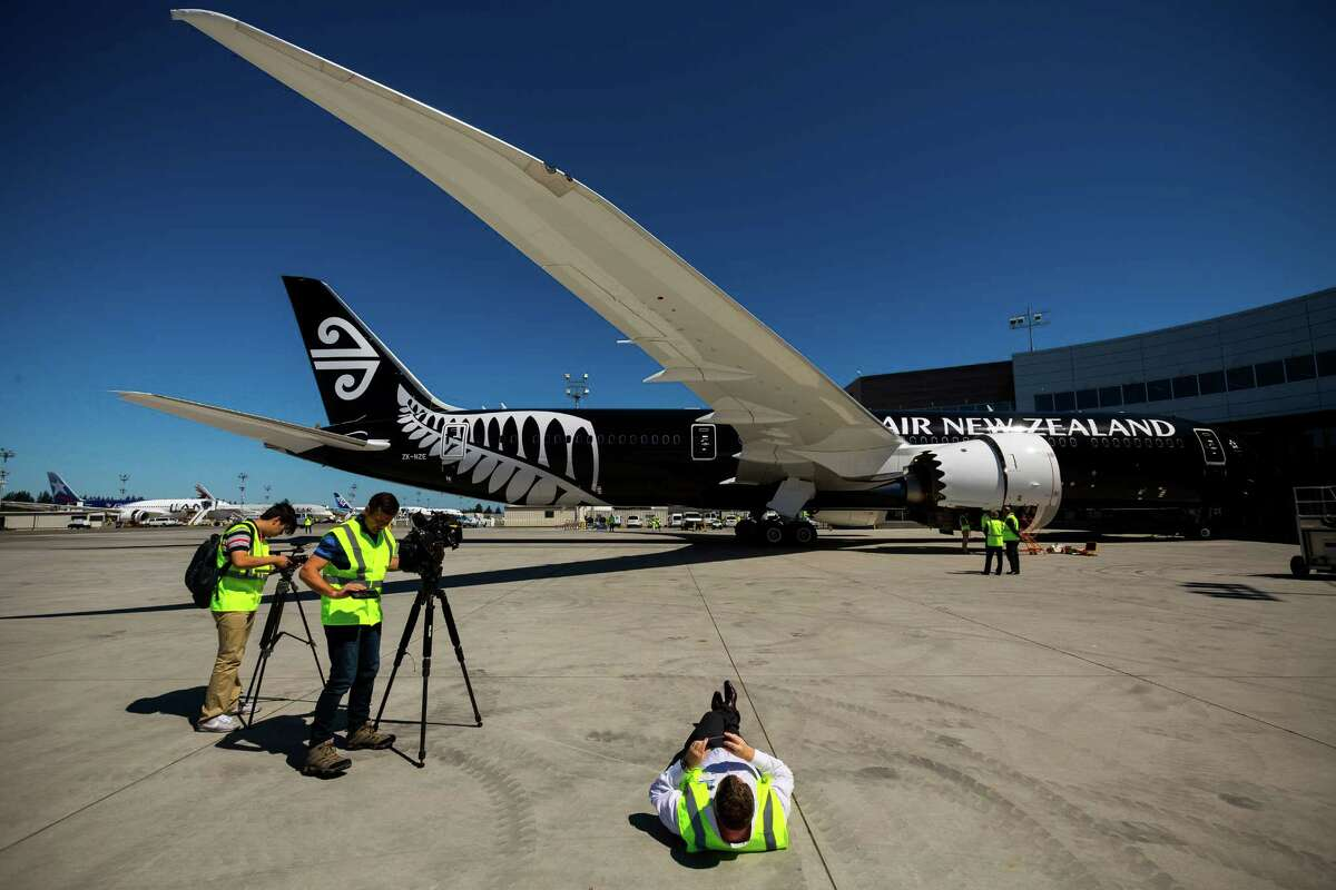 Members of the media get creative to make pictures of Air New Zealand's much anticipated Boeing 787-9 Dreamliner Wednesday, July 9, 2014, at the Boeing site in Everett, Wash. The aircraft will depart Seattle July 10 and arrive in Auckland on Friday, July 11.