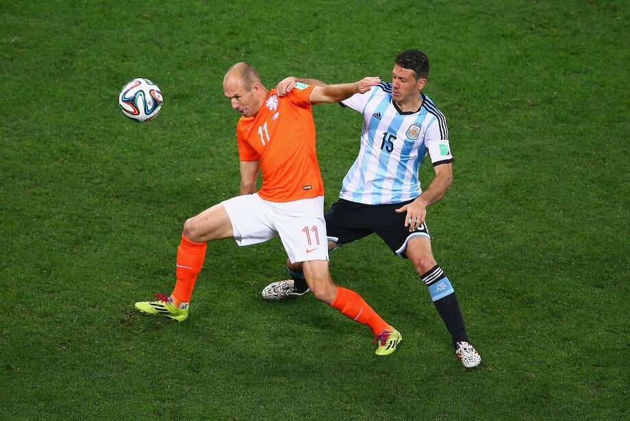 Arjen Robben of the Netherlands and Martin Demichelis of Argentina compete for the ball during the 2014 FIFA World Cup Brazil Semi Final match between the Netherlands and Argentina at Arena de Sao Paulo on July 9, 2014 in Sao Paulo, Brazil.  Photo: Julian Finney, Getty Images