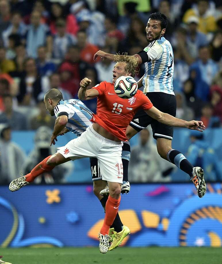 Netherlands' Dirk Kuyt is challenged by Argentina's Javier Mascherano, left, and Ezequiel Garay during the World Cup semifinal soccer match between the Netherlands and Argentina at the Itaquerao Stadium in Sao Paulo Brazil, Wednesday, July 9, 2014. Photo: Martin Meissner, Associated Press